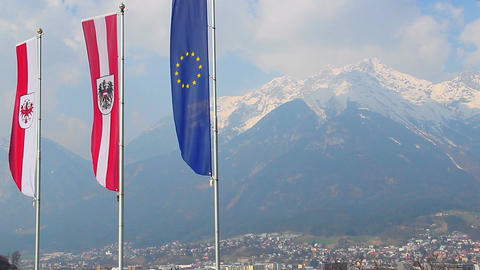 Flags with EU, Austria, Tyrol signs, majestic Alps on background Footage