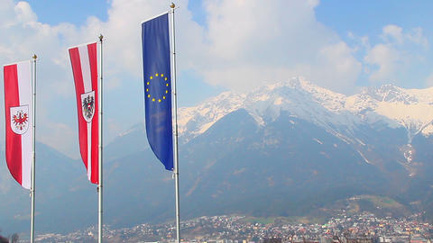 Flags with EU, Austria, Tyrol emblems waving in air, mountains Footage
