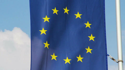 Flag of European Union waving in wind, blue sky background Live Action