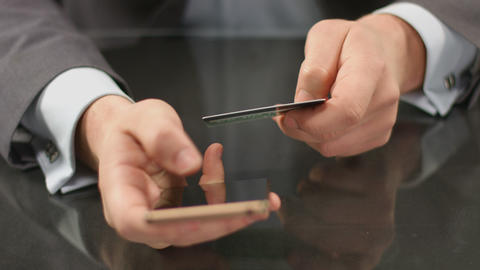 Boss using mobile banking on smartphone, inserting card number Footage