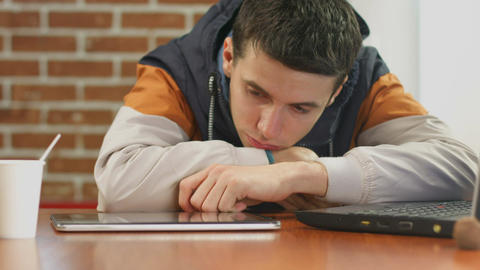 Bored student reading bad news on tablet, alone in cafe Live Action