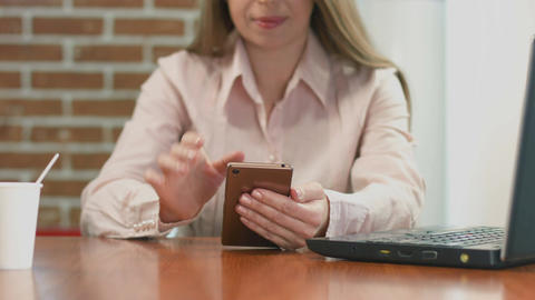 Happy female freelancer working on smart phone, watching video Footage