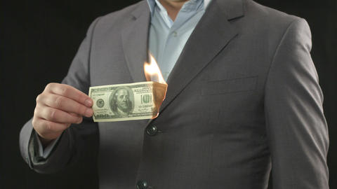 One hundred dollar bill on fire. Going bankrupt, losing money Footage