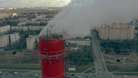 Aerial close-up view of the industrial smoke stack against urban residential Live Action