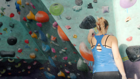 Attractive girl using powder preparing for activity then climbing wall in indoor Acción en vivo