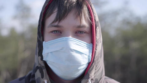 Close-up face of young Caucasian man in protective face mask outdoors. Portrait Live Action