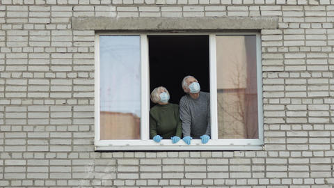 Old grandparents stay at window isolated at home on quarantine. Coronavirus Acción en vivo