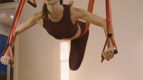Sporty woman practicing fly yoga in studio. Girl changing poses in air at studio Live Action