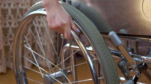 Young woman on a wheelchair. The girl moves in a wheelchair around the room Acción en vivo
