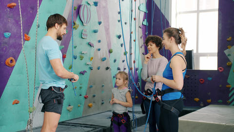 Male instructor talking to indoors climbing center customers about safety Live Action