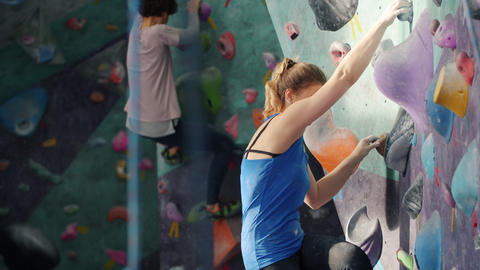 Young woman with ponytail applying chalk powder then climbing up vertical wall Acción en vivo