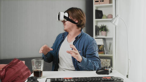 Young man using modern virtual reality glasses at home Acción en vivo