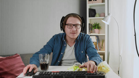 Pro streamer in headphones Plays in viedogame on His Personal Computer Live Action