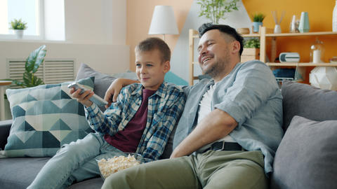 Middle-aged guy father watching TV with cheerful son relaxing on couch in house Live Action