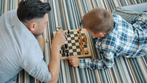 High angle view of man and smart child playing chess at home then doing high Live Action