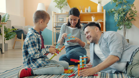 Happy family mother, father and son playing with construction toys at home Acción en vivo