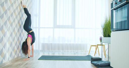 Woman is doing handstand to the wall, gymnastics at home, quarantine, 4k Acción en vivo