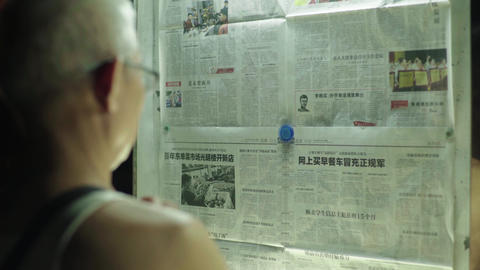 Pensioner reading a newspaper. Beijing. China. Asia Live Action