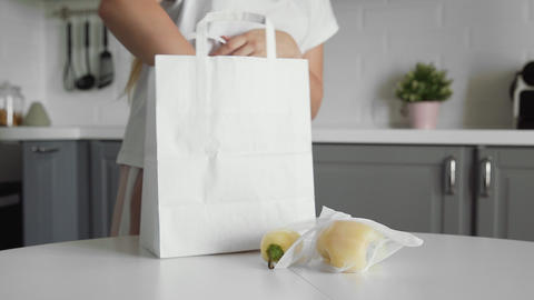 Close up of Young woman unpacking shopping bag with vegetables on the kitchen on Acción en vivo