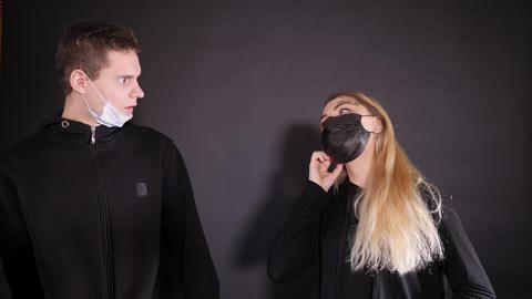 Guy with a girl in a medical mask. A man sprays a woman from a yellow balloon Acción en vivo