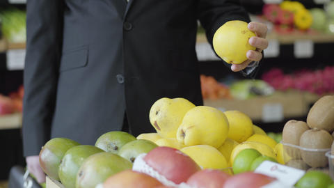 Unrecognizable young Caucasian man selecting yellow pears in grocery. Male vegan Live Action