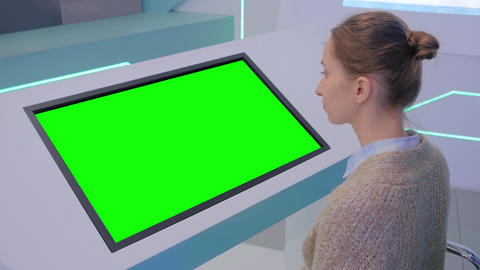 Woman looking at blank green display kiosk at exhibition - green screen concept Acción en vivo