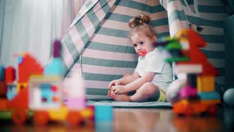 Unhappy frowned baby girl sits in toy teepee tent at home. Self-isolation Acción en vivo