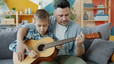 Dad teaching smal kid to play the guitar playing musical instrument in apartment Acción en vivo