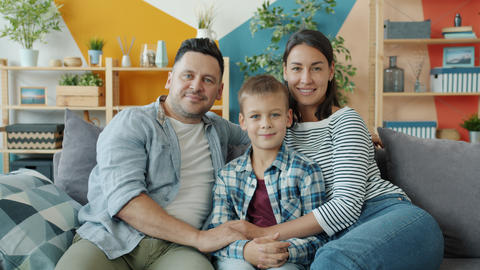 Portrait of happy family mother, father and son sitting on sofa at home smiling Acción en vivo