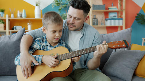 Adorable boy playing the guitar under guidance of caring father learning at home Live Action