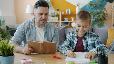 Creative child drawing pictures while father reading book sitting at desk Acción en vivo
