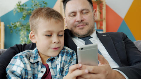 Cute child using smartphone with father businessman touching screen at home Acción en vivo