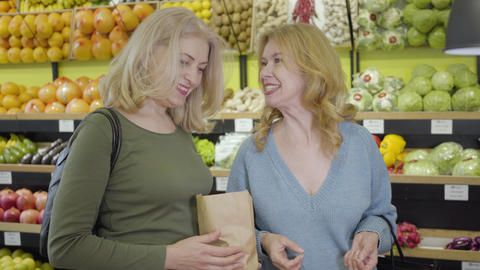 Positive Caucasian senior housewives gossiping and laughing as making purchases Live Action