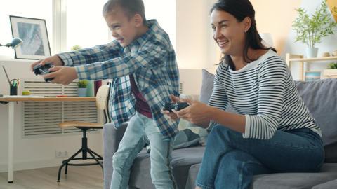 Mother and active boy playing video game in apartment having fun together Acción en vivo
