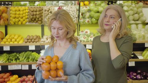 Beautiful senior Caucasian woman smelling fresh tasty tangerine as her female Live Action