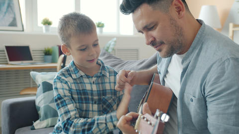 Joyful kid having fun with guitar while caring dad creative man teaching him to Acción en vivo