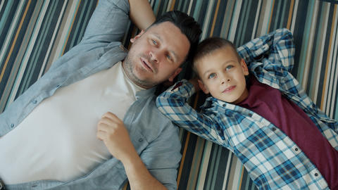 Portrait of adult man and cute boy lying on house floor talking relaxing Acción en vivo