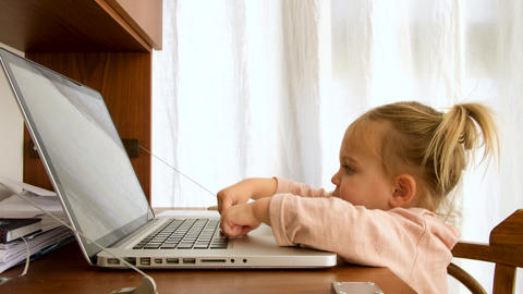 Smart little toddler girl using her laptop Acción en vivo