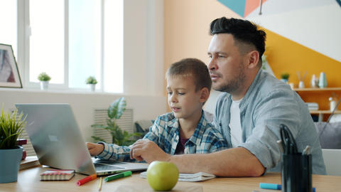 Little boy learning online using laptop while father helping sitting at table in Live Action