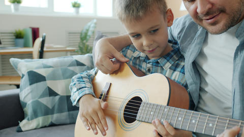 Slow motion of father and son playing the guitar, child learning to use musical Live Action