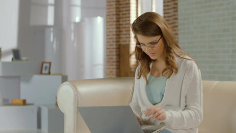 Young female freelancer in glasses typing e-mail, using laptop Footage