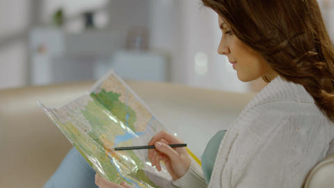 Pretty lady planning trip for weekend, vacation, studying map Footage