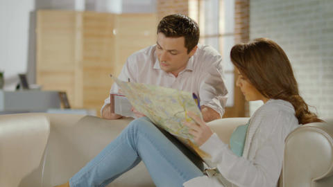 Happy just married couple planning honeymoon trip, checking map Footage