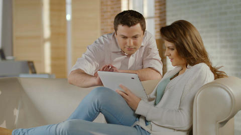 Happy young couple watching family photos on tablet PC, memories Footage