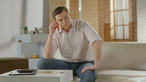 Man getting serious phone call at home, bad news, problem Footage