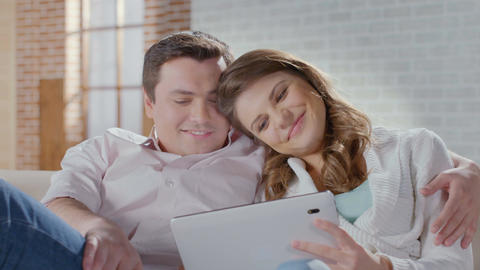 Smiling wife husband shopping online, choosing items on tablet Footage
