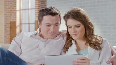 Couple chatting, view photos on tablet, laughing in living room Footage