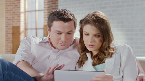 Middle-aged couple talking, laughing, viewing photos on tablet Footage