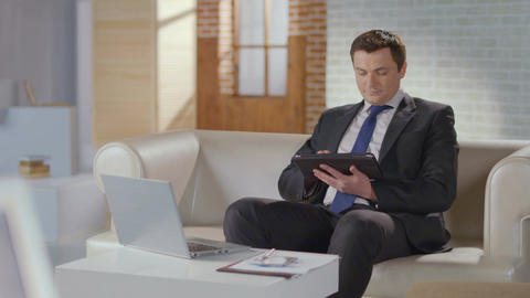 Businessman typing, scrolling pages on tablet, looking at camera Footage