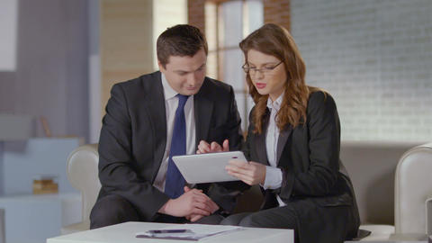Real estate agent showing photos on tablet to businessman client Footage